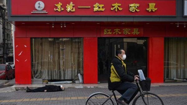 法新社刊登的照片,一名手拿購物袋的老人倒斃武漢街頭。(HECTOR RETAMAL/AFP via Getty Images)