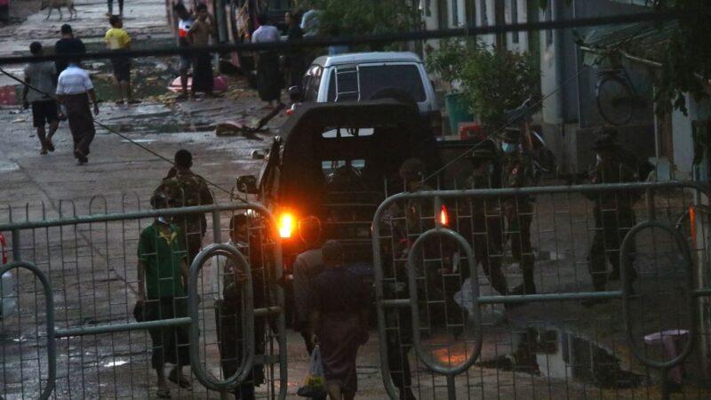 2021年4月6日,仰光南奧卡拉帕鎮的一個汽車站發生爆炸後,在鎮壓反對軍事政變的抗議活動中,安全部隊在入口大門旁站崗。(STR/AFP via Getty Images)