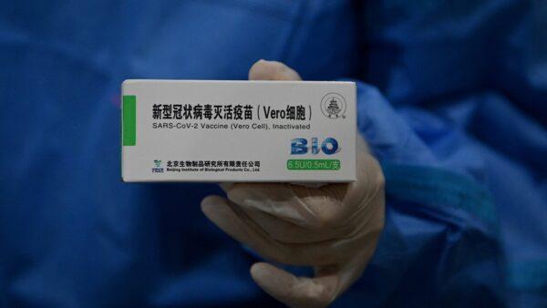 一名醫務人員展示了一盒中共國產國藥疫苗。( NOEL CELIS/AFP via Getty Images)