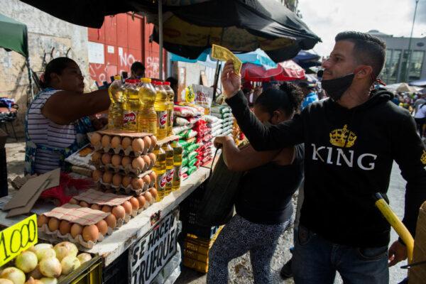2020年12月5日,一名男子(右)在加拉加斯的一個市場檢查一張美元鈔票。(CRISTIAN HERNANDEZ/AFP via Getty Images)