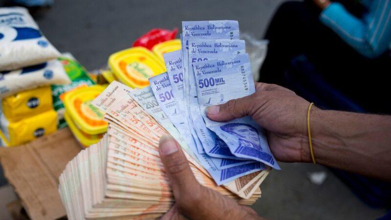 2021年4月6日,一名男子在加拉加斯的卡蒂亞社區的一個街頭市場拿著一疊玻利瓦鈔票。(PEDRO RANCES MATTEY/AFP via Getty Images)
