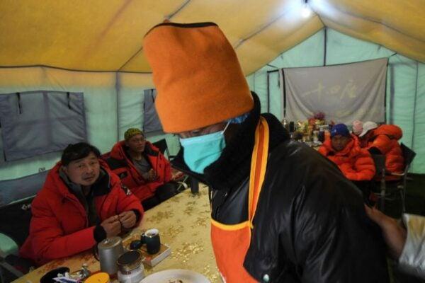 2021年5月1日拍攝的照片中,一名探險隊工作人員戴著口罩在珠峰大本營的食堂帳篷內工作。珠穆朗瑪峰爆發中共病毒,數十人被直升機從世界最高峰腳下疏散,破壞了尼泊爾創紀錄的登山季節計劃。(PRAKASH MATHEMA/AFP via Getty Images)