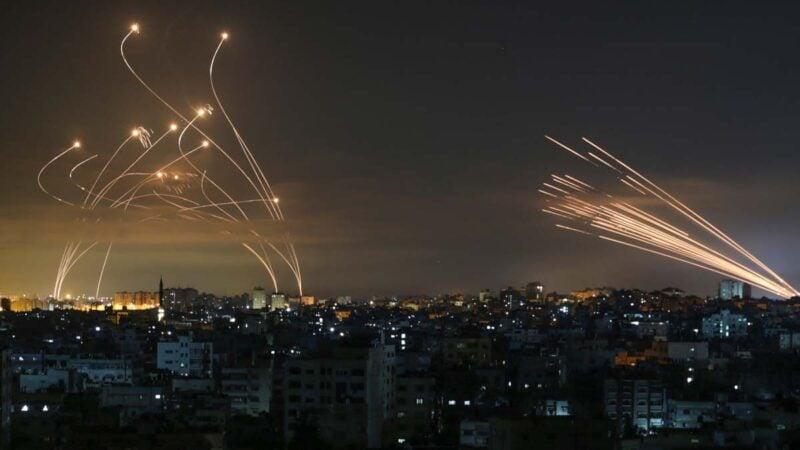 2021年5月14日,以色列「鐵穹」導彈(左)升空、攔截哈馬斯火箭彈(右)的場面。(ANAS BABA/AFP via Getty Images)