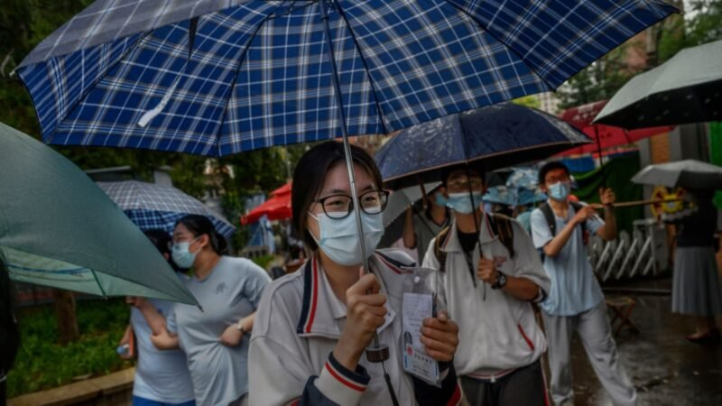 2020年7月9日,中國北京市一所高中的學生們參加完全國高考後,撐著雨傘離開考場。(Kevin Frayer/Getty Images)