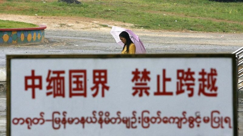2007 年 9 月 27 日,中國雲南省中緬邊境線上,一名緬甸婦女從邊界警告牌旁邊經過。(STR/AFP via Getty Images)