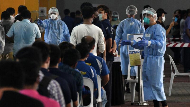 2020 年 6 月 10 日,新加坡工人在返工之前正進行中共病毒(俗稱武漢病毒、新冠病毒、COVID-19)鼻拭子測試。(ROSLAN RAHMAN/AFP via Getty Images)