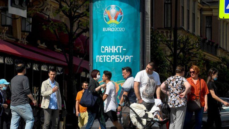 2021年6月6日在聖彼得堡,2020年歐洲足球錦標賽開始前五天,人們走過一張2020年歐洲足球錦標賽的海報。(OLGA MALTSEVA/AFP via Getty Images)
