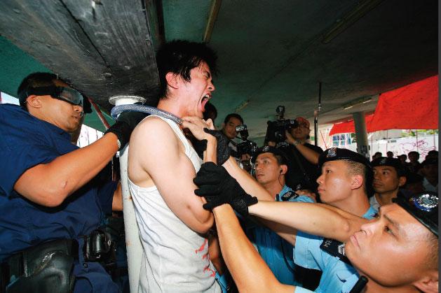 在皇后碼頭地面平台最後一位被帶離場的林輝,他一度用鐵鍊將自己鎖在皇后碼頭柱上,最後警方剪開他頸上的鐵鍊,並由7至8名警員將他抬走。(AFP)