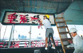 當局昨日拆卸皇后碼頭的中文牌匾,所有物件將運往大嶼山爆炸品儲存倉存放,待日後重組。圖為8月1日,當局清場後,工人將所有保育人士的抗議橫額拆掉。(SAMANTHA SIN/AFP/Getty Images)