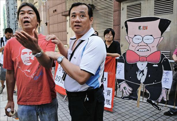 梁國雄(左)昨日拉票之餘不忘向行政長官曾蔭權抗議。他是在地區直選各候選人中唯一在政綱中要求追究六四屠城責任、結束一黨專政以及爭取普選的候選人。(AFP)