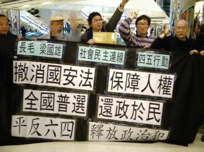 梁國雄與10多名四五行動及社民連成員展示抗議橫幅,提出訴求。(大紀元)