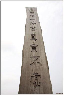 遊人經過長高的木條,需要仰望才可能勉強看到經文的全句子。(大紀元)