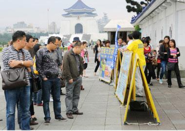 4月25日在台北中正紀念堂,大陸遊客駐足觀看法輪功真相。(大紀元)