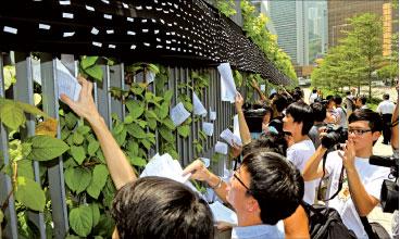 由於特首梁振英拒絕接收支持撤回洗腦科的10萬市民簽名,學民思潮成員將簽名塞在特首辦圍欄上。(攝影:潘在殊/大紀元)