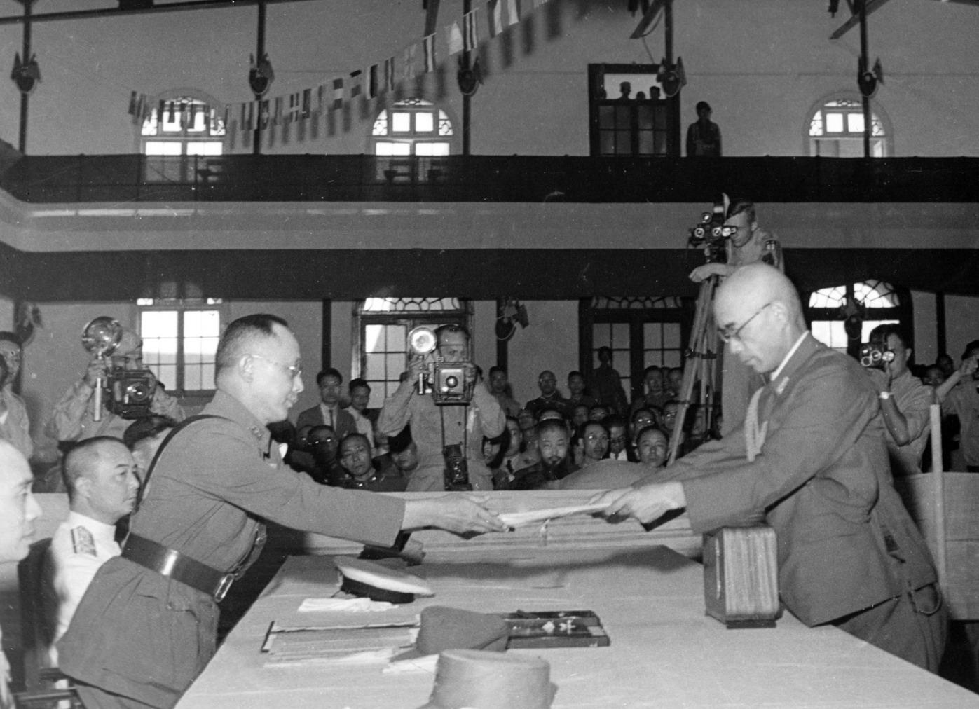 1945年9月2日國軍何應欽總司令(左)接受日本中國派遣軍總參謀長小林淺三郎呈遞降書。(網絡圖片)