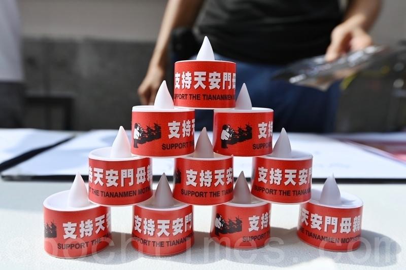 支聯會向市民派發電子蠟燭,寫著「支持天安門母親」。(宋碧龍/大紀元)