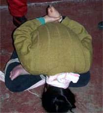 「球形綑綁」示意圖。頭頸和雙盤著的腳捆在一起。(明慧網)