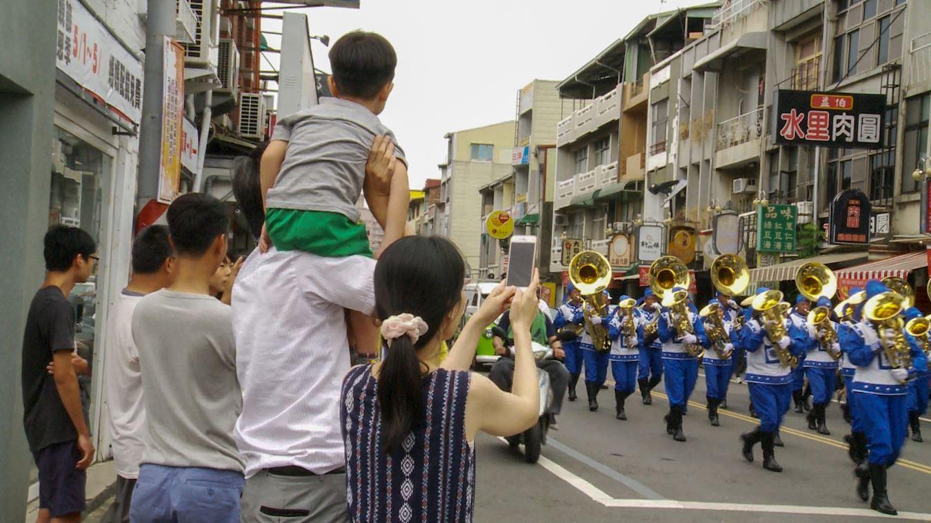 不少市民拿手機爭相對著行進中的天國樂團拍照。(明慧網)