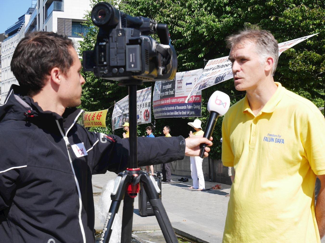 比利時媒體布魯塞爾電視台記者現場採訪法輪功學員。(明慧網)