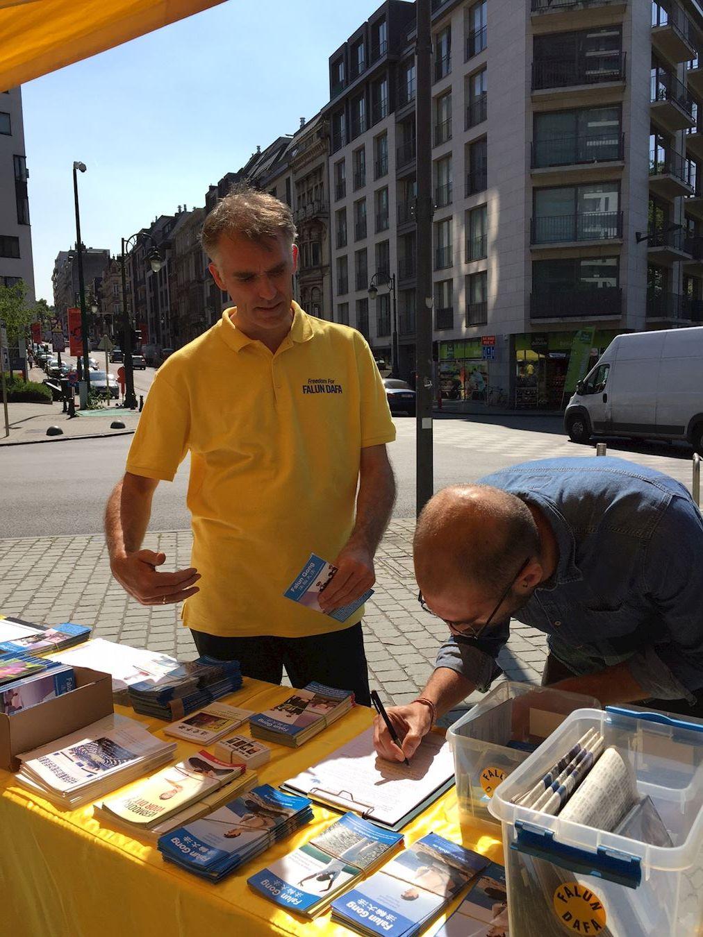 在歐洲議會工作的大衛(David Prino)在《要求比利時政府討論制止發生在中國的活摘法輪功學員器官的罪行》的征簽簿上簽名。(明慧網)