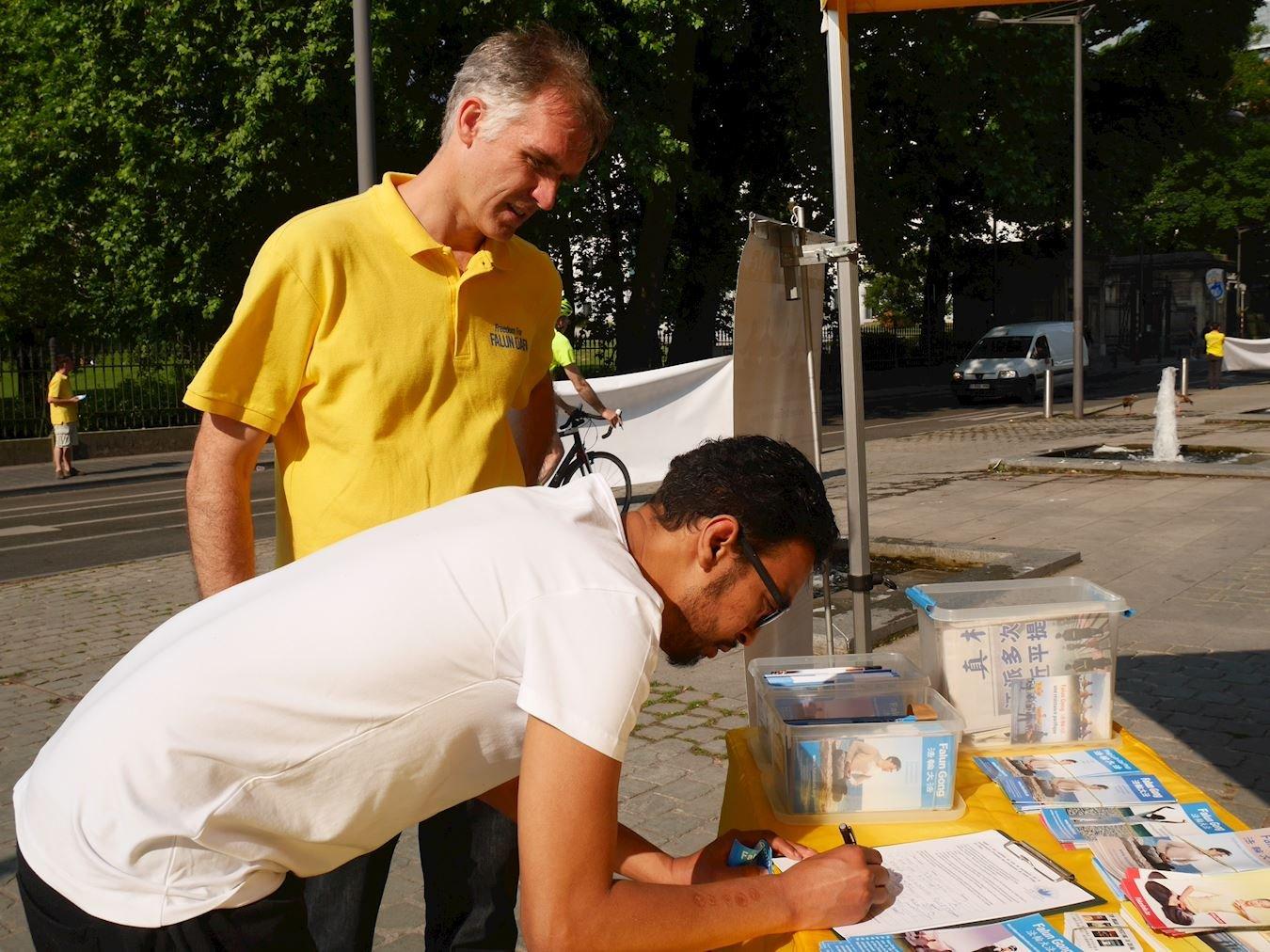 默罕默德(Mohammad)在要求比利時政府反對活摘法輪功學員器官的證簽簿上簽名。(明慧網)